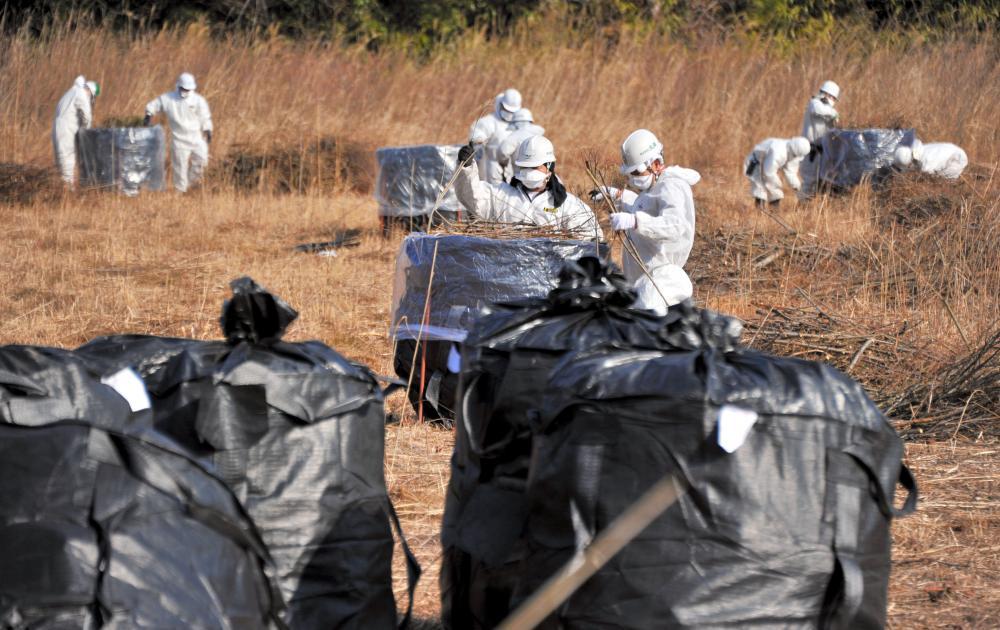 写真・図版 : 帰還困難区域での除染作業=2016年3月、福島県富岡町、仙波理撮影