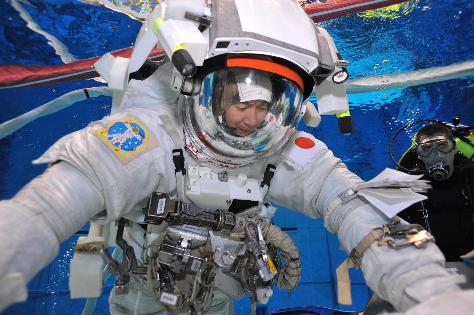 写真・図版 : プールの中で無重力の空間を模擬するには、ダイバーのサポートが必要不可欠(JAXA/NASA)