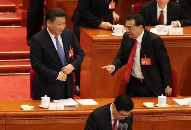 全人代の開幕日、人民大会堂から退席する際に言葉を交わす習近平国家主席(左)と李克強首相=3月5日、中国・北京