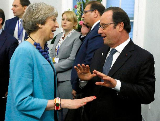 写真・図版 : 欧州連合(EU)の首脳会合が開かれるマルタの首都バレッタで2月3日、言葉を交わすメイ英首相(左)とオランド仏大統領=ロイター