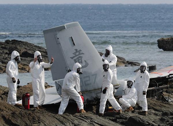 大破したオスプレイの機体の切断作業をする米軍関係者ら=2016年12月16日、沖縄県名護市、関田航撮影