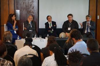 写真・図版 : 南アフリカ科学フォーラムでのパネル討論。持続可能な社会に向けた科学者の公衆関与について議論した。壇上中央が筆者=JST提供