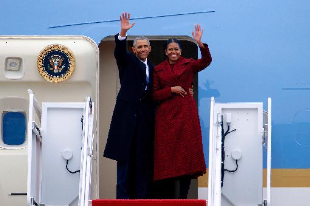 写真・図版 : 1月20日、米メリーランド州のアンドルーズ空軍基地から飛行機に乗り込む際、ミシェル夫人と手を振るオバマ前大統領=ロイター