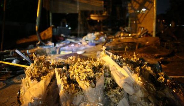 襲撃テロが起きたレストランの前には花束が置かれていた。奥は破壊されたピザ小屋=2016年7月、ダッカ