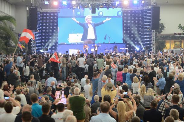 ウィーン郊外での集会に登場したルペン党首をオーストリア国旗で歓迎する人々=2016年6月