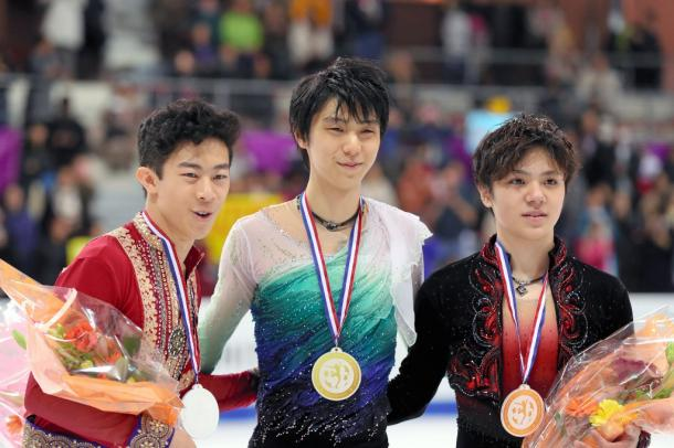 GPファイナル de優勝してメダルを見せる羽生結弦(中央)。2位のネイサン・チェン(左)、3位の宇野昌磨