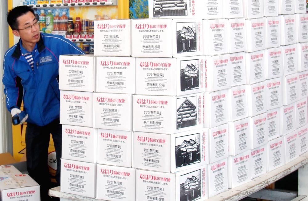 写真・図版 : 地元産品が詰まった返礼品の発送作業=高知県奈半利町