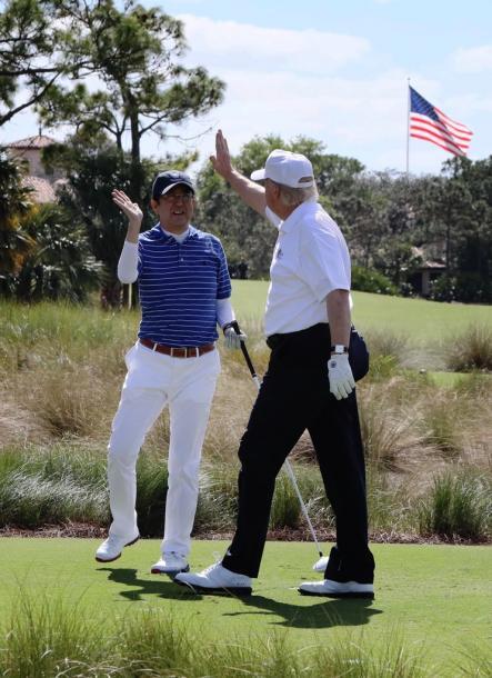 米フロリダ州・パームビーチでゴルフを楽しみ、ハイタッチをする安倍晋三首相(左)とトランプ大統領=11日、内閣広報室提供