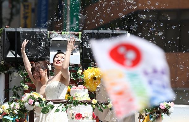 性的少数者への理解を求めるパレードに参加し、沿道などに手を振る人たち=2016年5月8日、東京都渋谷区