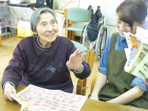 夕食の買い物に行くために、スーパーのチラシを見て職員と相談する認知症の波多野和さん=2016年3月14日、北海道恵庭市