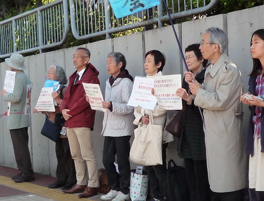 写真・図版 : 総会の会場前で軍事研究の反対を訴える人たち=4月14日、東京・六本木