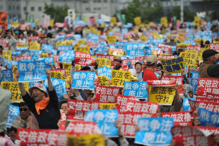 写真・図版 : 2016年の憲法記念日の集会で、かけ声に合わせてプラカードを掲げる人たち=東京都江東区