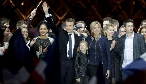 パリ・ルーブル美術館の前で勝利演説を終え、支持者にあいさつするマクロン氏(中央左)とブリジット夫人(中央右)=5月7日