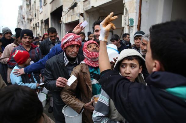 写真・図版 : シリア・アレッポ東部のマサケン・ハナノ地区で食料の配給を受ける人々=2017年1月9日