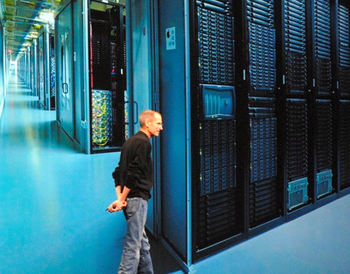写真・図版 : 巨大データセンターの映した映像の前で、クラウドサービスを紹介するアップルのスティーブ・ジョブズ氏=2011年6月、サンフランシスコ