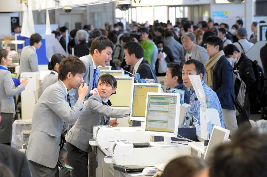 写真・図版 : 情報サービス産業は社会の基盤を支えている。システム障害によって混雑する空港カウンター=2016年3月、大阪
