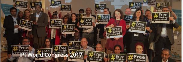 写真・図版 : IPI世界大会で、トルコ人ジャーナリストを解放せよというプラカードを掲げる参加者たち(IPIのウェブサイトより)
