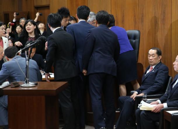 野党委員が委員長席に詰めかける中、組織的犯罪処罰法の改正案の採決を待つ金田勝年法相(右)=19日20170519