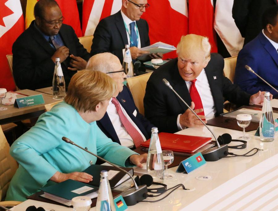写真・図版 : G7サミットで言葉を交わすトランプ米大統領(右)とメルケル独首相(左端)=5月27日、イタリア南部シチリア島