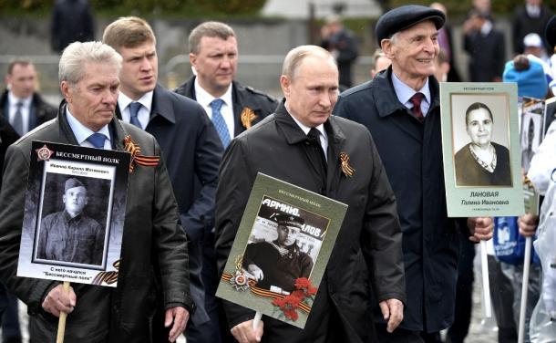 兵士姿の父親ウラジーミルさんの写真を手にモスクワの「不滅の連隊」行進に参加したプーチン大統領(中)=2017年5月9日、ロシア大統領府ホームページから
