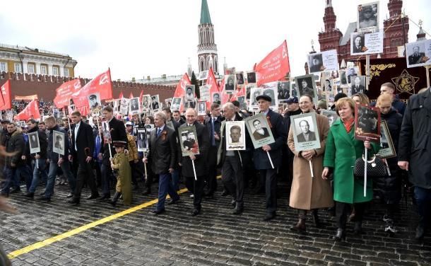 写真・図版 : モスクワの「赤の広場」での「不滅の連隊」行進。中央に兵士姿の父親ウラジーミルさんの写真を手にしたプーチン大統領も見える=2017年5月9日、ロシア大統領府ホームページから