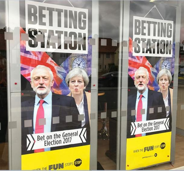コービン党首(左)の労働党が勝つかメイ首相の保守党が勝つか?賭け屋のウィンドーに貼られたポスター