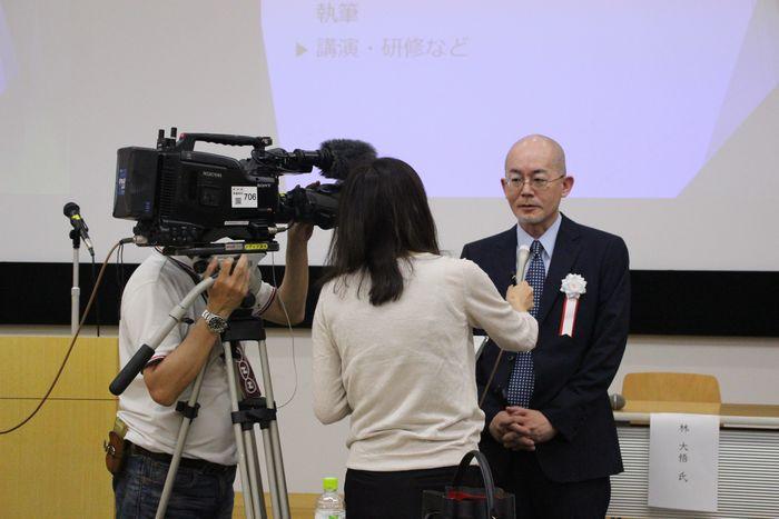 写真・図版 : 治療的司法研究センター設立記念の講演会で取材を受ける指宿信センター長=6月10日、成城大学