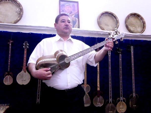 写真・図版 : 桑の木と牛の心臓の皮で作った民族楽器を演奏する楽人=撮影・筆者