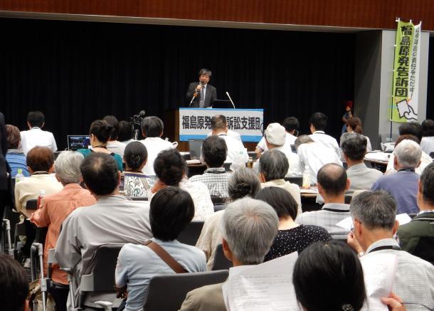 参議院議員会館に集まった被災者らに初公判の説明をする海渡雄一弁護士=6月30日