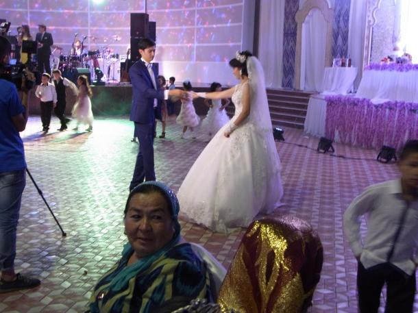 写真・図版 : 大勢の参列者を前に結婚式で踊る新郎と新婦(サマルカンドで)=撮影・筆者