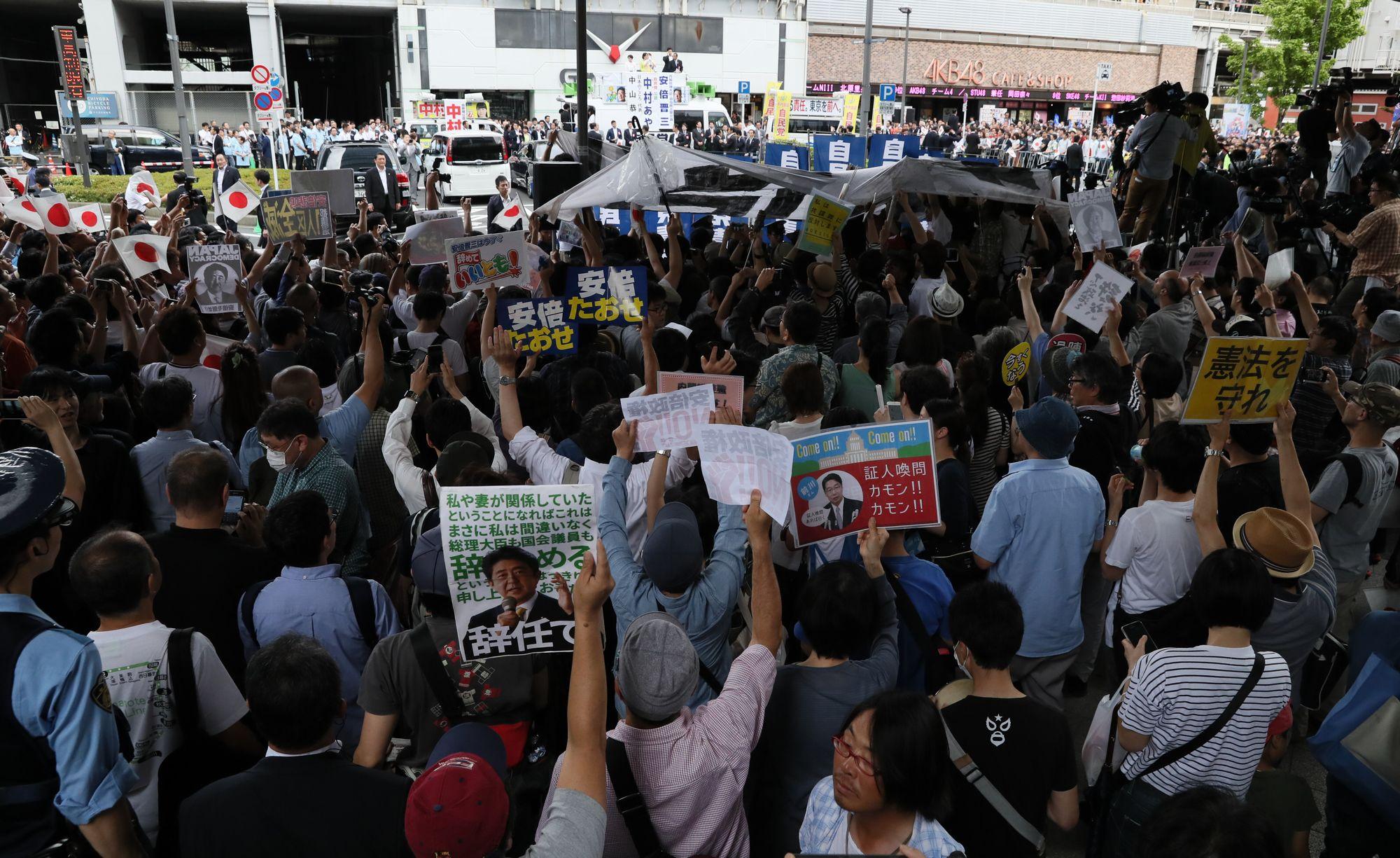 写真・図版 : 都議選での安倍晋三首相の街頭演説にプラカードを掲げて抗議する人たち=7月1日、東京都千代田区