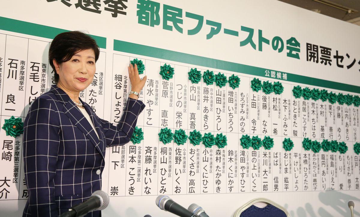当選の花がついたボードの前に立つ「都民ファーストの会」の小池百合子代表=2日