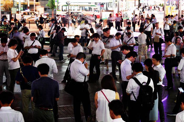 写真・図版 : スマートフォン片手に仮想空間の目印を求めてゲームを楽しむ人たち=2016年8月、東京都豊島区