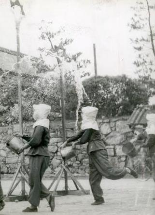 写真・図版 : 仮標にバケツの水を注ぐ訓練をする広島師団司令部女子職員たち=1943年6月