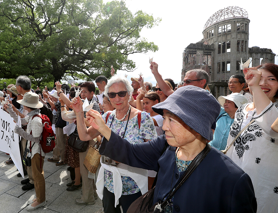 写真・図版 : 折り鶴を掲げて、核兵器禁止条約採択を歓迎する人たち=7月8日、広島市