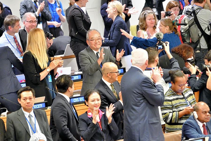 写真・図版 : 核兵器禁止条約が採択され、わき上がる国連本部の議場=7月7日、ニューヨーク