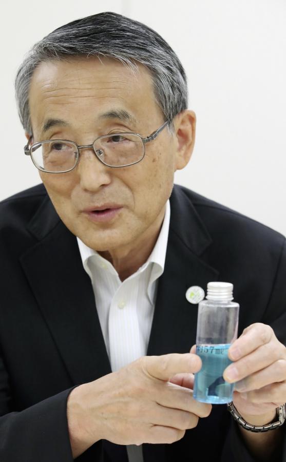 写真・図版 : トリチウム水の総量を容器で示す田中俊一委員長=2017年8月24日、早坂元興撮影