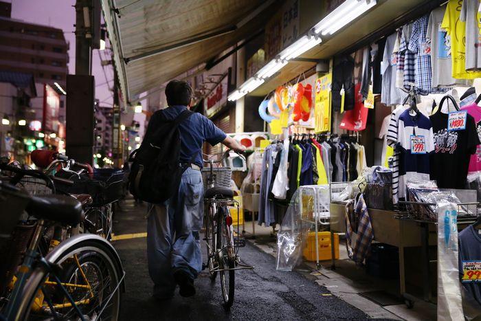 写真・図版 : 自転車を押して家路につく男性。非正規の警備員で、生活は苦しい=東京都内