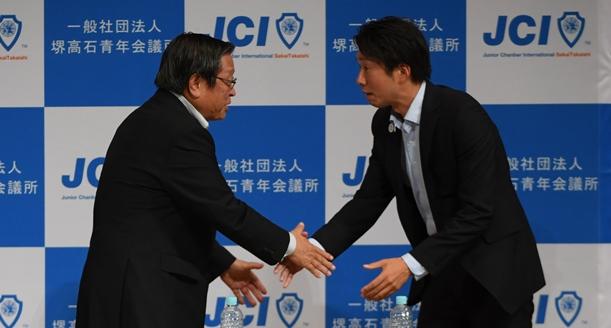 堺市長選に向けた公開討論会の終わりに握手する竹山修身氏(左)と永藤英機氏=2017年9月7日、堺市中区