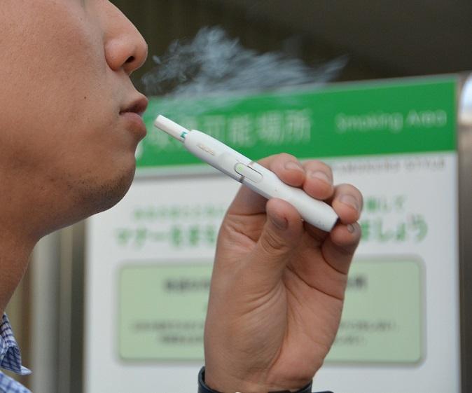 写真・図版 : 加熱式たばこ「アイコス」を吸う男性。白く見えているのは、煙ではなく蒸気=2017年9月、森田貴之撮影