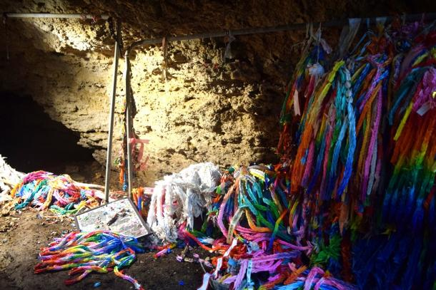 チビチリガマの入り口に供えられていた千羽鶴は、引きちぎられて地面に散乱していた=12日午後4時29分、沖縄県読谷村20170912