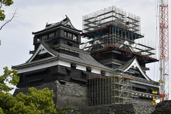 写真・図版 : 修復のため解体作業が進む熊本城の大天守(右)。左は小天守=2017年5月13日、熊本市