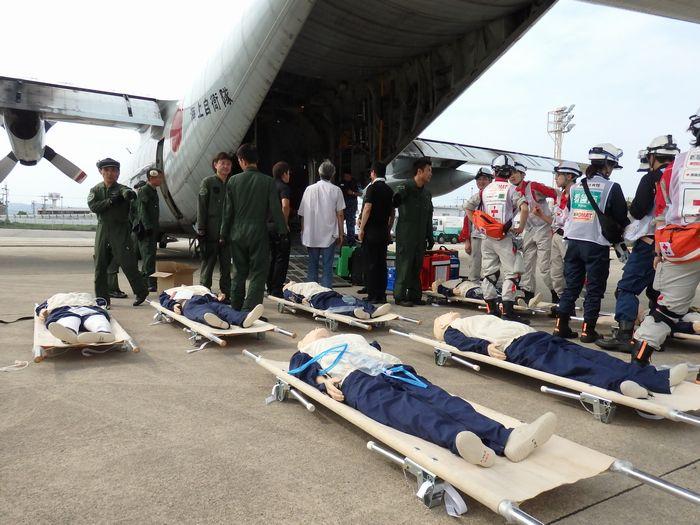 写真・図版 : 巨大地震を想定した医療訓練で、海上自衛隊の輸送機に搬入される患者役の人形=伊丹空港