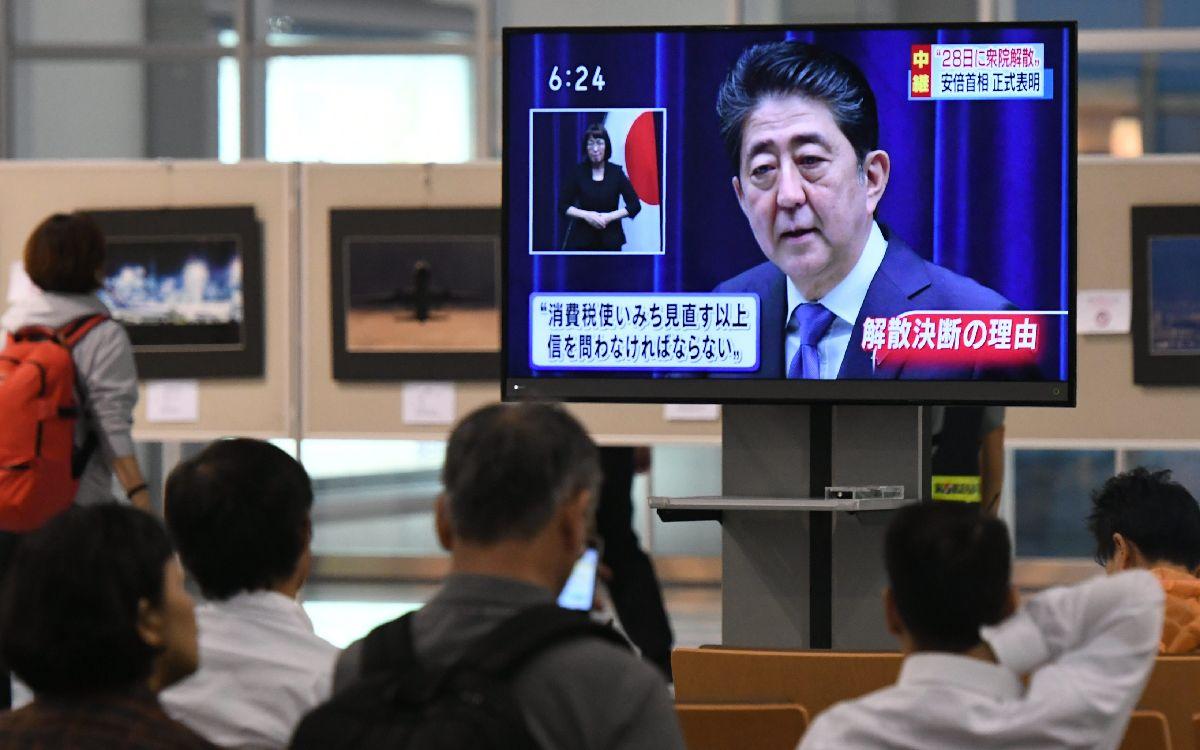 衆院解散を表明する安倍首相のニュースに見入る人たち=25日午後6時11分、福岡市博多区の福岡空港