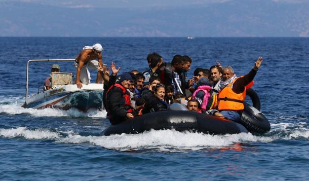 シリアなどを逃れた難民らを乗せたボートに近づく密航業者の男(左)。上陸後、ボートからエンジンを外して車に積み込んでいた=13日午後、ギリシャ・レスボス島2015