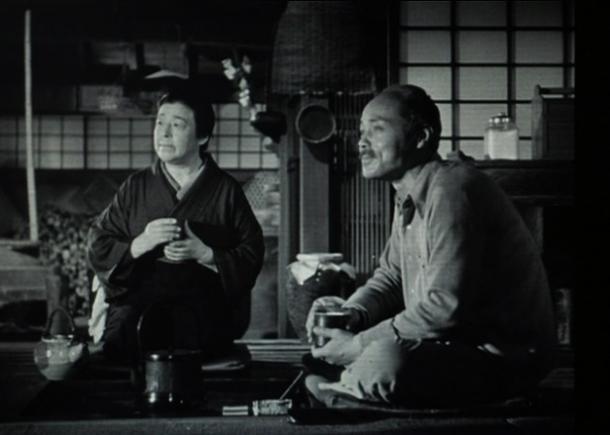写真・図版 : 【写真11】 囲炉裏の前で左向きに座り、花嫁行列を見ながら「紀子はどうしているしょう」と語りあう間宮家の老夫婦(菅井一郎と東山千栄子)