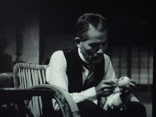 写真・図版 : 【写真4】 右斜め向かいに椅子に座り、リンゴの皮を剥く笠智衆