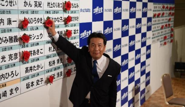 当選を決めた候補者名に花をつける立憲民主党の枝野幸男代表=10月23日午前1時、東京都港区
