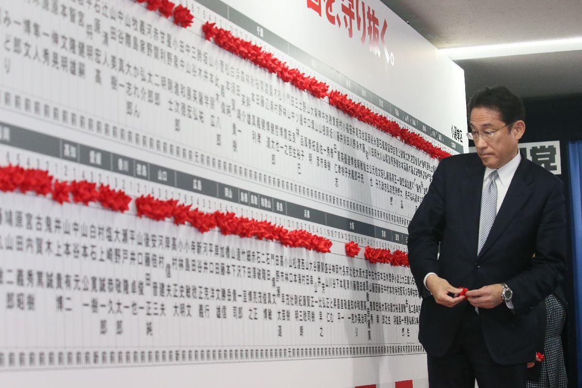 写真・図版 : 当選を決めた候補者名に花をつける自民党の岸田文雄政調会長=10月22日午後11時36分、東京・永田町