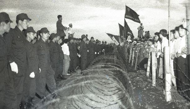 立川基地内民有地収用の測量の警備に出動した警官隊と有刺鉄線のバリケード越しににらみ合う反対派労組員、学生、地元民=1957年7月8日東京都北多摩郡砂川町